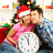 Young happy couple holding clock near Christmas tree at home — Stock Photo #15845613