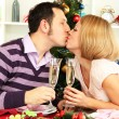 Young happy couple holding glasses with champagne at table near Christmas tree — Stock Photo #15845627