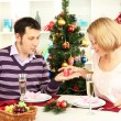 Young happy couple with presents sitting at table near Christmas tree — Stock Photo #15845649