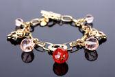 Beautiful golden bracelet with precious stones on grey background — Stock Photo