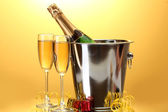 Champagne bottle in bucket with ice and glasses of champagne, on yellow background — Stock Photo