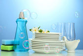 Empty clean plates and glasses with dishwashing liquid, sponges and flowers on blue background — Stock Photo