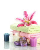 Towels with lily, aroma oil, candles and soap isolated on white — Stock Photo