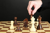 Businessman playing chess isolated on black — Stock Photo