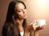 Beautiful young woman with cup of coffee, on brown background — Стоковое фото