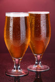 Glasses of beer on pink background — Stock Photo