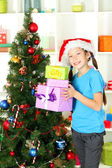 Little girl holding gift boxes near christmas tree — Stock Photo