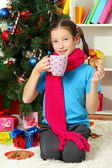Little girl with pink scarf and cup of hot drink sitting near christmas tree — Foto de Stock