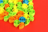 Colorful quilling on red background close-up — Stok fotoğraf