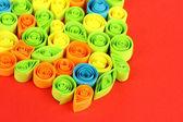 Kolorowy, quilling na czerwonym tle z bliska — Zdjęcie stockowe