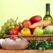 Composition with vegetables  in wicker basket on green background - Stock Photo