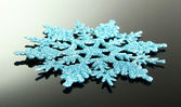 Beautiful snowflake on grey background — Stock Photo