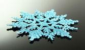 Beautiful snowflake on grey background — Stockfoto