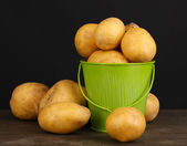 Ripe potatoes in pail on wooden table on black background — Stock Photo
