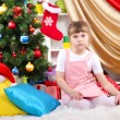 Stock Photo: Little girl sitting near Christmas tree in festively decorated room