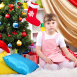 Little girl sitting near the Christmas tree in festively decorated room — Stock Photo #15985417
