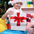 A little girl opens a gift in festively decorated room — Stock Photo #15985451