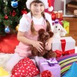 Little girl in Santa hat near the Christmas tree in festively decorated room — Stock Photo #15985525