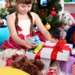 Stock Photo: Beautiful little girl is happy gift in festively decorated room