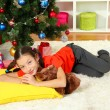 Little girl sleeping near christmas tree — Stock Photo #15987293