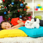 Little girl sleeping near christmas tree — Stock Photo #15987355