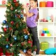 Little girl decorating christmas tree — Stock Photo #15987459