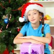 Little girl holding gift box near christmas tree — Stock Photo #15987549