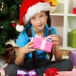 Little girl holding gift box near christmas tree - Stock Photo