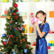 Little girl holding gift box near christmas tree — Stock Photo #15987733