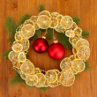 Christmas wreath of dried lemons with fir tree and balls, on wooden background — Стоковая фотография