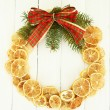 Christmas wreath of dried lemons with fir tree and bow, on white wooden background — Foto de Stock