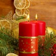 Two candles and christmas decorations, on wooden background - Stock Photo