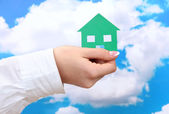 Concept: woman hand with paper house on sky background, close up — Stock Photo