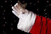 Santa claus hand met Kerstster op lichte achtergrond — Stockfoto