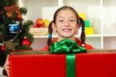 Petite fille avec grand coffret près de sapin de Noël — Photo