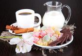 šálek kávy s rahat potěšení a mléko na dřevěný stůl — Stock fotografie