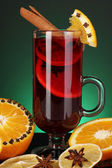 Fragrant mulled wine in glass with spices and oranges around on green background — Stock Photo