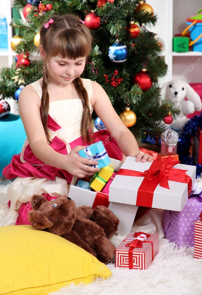 Beautiful little girl is happy gift in festively decorated room — Stock Photo #15985573