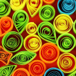 Colorful quilling on red background close-up - Zdjęcie stockowe