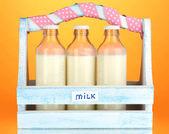 Mleko w butelkach w drewniane pudełko na pomarańczowym tle — Zdjęcie stockowe