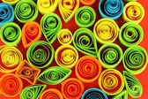 Colorful quilling on red background close-up — Zdjęcie stockowe