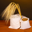 Flour and wheat grain on wooden table on dark background — Stock Photo
