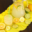 Citrus lemonade in glass and pitcher of citrus around on yellow fabric on wooden table close-up — Foto de Stock