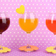 Stock Photo: Colorful cocktails with bright decor for glasses on purple background with polka dots