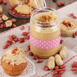 Delicious peanut butter in jar with baking on napkin on wooden table close-up - Stock Photo