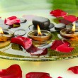 Spa stones with rose petals and candles in water on plate — Stock Photo #16021693