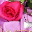 Beautiful pink rose with heart pendant — Stock Photo