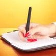 Hand signing in notebook  on wooden table on color background - Stock Photo