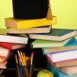 Books and magister cap against school board on wooden table on green background - Zdjcie stockowe
