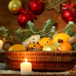 Christmas composition in basket with oranges and fir tree, on wooden background - Stock Photo